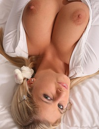 Busty blonde gets comfy on her bed